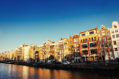 Beautiful night in Amsterdam, illumination of buildings and boat Stock Photo