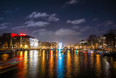 Beautiful night city canals of Amsterdam with moving passanger boat. AMSTERDAM, NETHERLANDS - JANUARY 12, 2017: Beautiful night city canals of Amsterdam with Stock Photos