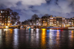 Beautiful night city canals of Amsterdam with moving passanger boat. AMSTERDAM, NETHERLANDS - JANUARY 12, 2017: Beautiful night city canals of Amsterdam with Stock Images