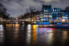 Beautiful night city canals of Amsterdam with moving passanger boat. AMSTERDAM, NETHERLANDS - JANUARY 12, 2017: Beautiful night city canals of Amsterdam with Stock Photo