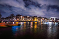 Beautiful night city canals of Amsterdam with moving passanger boat. AMSTERDAM, NETHERLANDS - JANUARY 12, 2017: Beautiful night city canals of Amsterdam with Stock Image