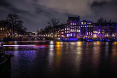 Beautiful night city canals of Amsterdam with moving passanger boat. AMSTERDAM, NETHERLANDS - JANUARY 12, 2017: Beautiful night city canals of Amsterdam with Royalty Free Stock Photo