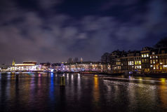 Beautiful night city canals of Amsterdam with moving passanger boat. AMSTERDAM, NETHERLANDS - JANUARY 12, 2017: Beautiful night city canals of Amsterdam with Royalty Free Stock Images