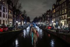 Beautiful night city canals of Amsterdam with moving passenger boat. AMSTERDAM, NETHERLANDS - JANUARY 12, 2017: Beautiful night city canals of Amsterdam with Royalty Free Stock Photo
