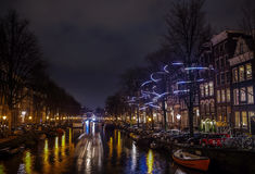 Beautiful night city canals of Amsterdam with moving passenger boat. AMSTERDAM, NETHERLANDS - JANUARY 12, 2017: Beautiful night city canals of Amsterdam with Royalty Free Stock Image