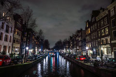 Beautiful night city canals of Amsterdam with moving passenger boat. AMSTERDAM, NETHERLANDS - JANUARY 12, 2017: Beautiful night city canals of Amsterdam with Stock Photography