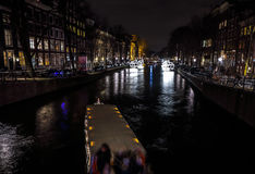 Beautiful night city canals of Amsterdam with moving passenger boat. AMSTERDAM, NETHERLANDS - JANUARY 12, 2017: Beautiful night city canals of Amsterdam with Royalty Free Stock Photography