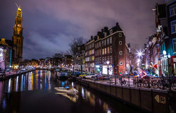 Beautiful night city canals of Amsterdam with moving passenger boat. AMSTERDAM, NETHERLANDS - JANUARY 12, 2017: Beautiful night city canals of Amsterdam with Stock Photo