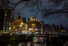 Beautiful night city canals of Amsterdam with moving passenger boat. AMSTERDAM, NETHERLANDS - JANUARY 12, 2017: Beautiful night city canals of Amsterdam with Royalty Free Stock Images