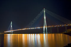 Beautiful night city lights. high bridge across the Bay stretched on pylons. In water reflected glare from the bridge Royalty Free Stock Photos