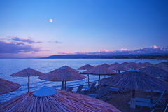 Beautiful night image of beach with umbrellas and sunbeds Royalty Free Stock Image