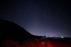 Beautiful night landscape of stars at sky and mountain silhouette near road with car trails. Road in the mountains under a starry Stock Images