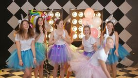 Beautiful night out girls dancing throwing gold confetti slow motion. Group of bride friendgirls in a fairy unicorn costumes, colorful air skirts dancing stock video footage