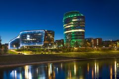 Beautiful night panorama of office buildings in Vilnius city. Beautiful modern and old buildings drops nice colorful illumination on river in night Lithuania Stock Photos