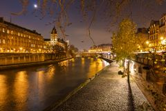 A beautiful night in Paris in France at the Seine river with street lights and trees Stock Photography