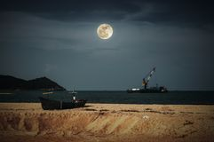 Beautiful night sky with bright full moon above cargo ship anchored in the sea. Traditional fishing boat parked on tropical beach stock photo