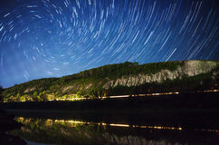 Beautiful night sky, the Milky Way, spiral star trails and the trees Stock Photos