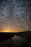 A beautiful night sky, spiral star trails and the forest Stock Photo
