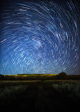 A beautiful night sky, spiral star trails and the forest Royalty Free Stock Photo