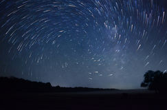 Beautiful night sky, spiral star trails and  forest Royalty Free Stock Photo