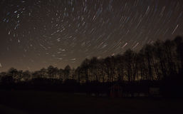 Beautiful night sky, spiral star trails and the forest Stock Images