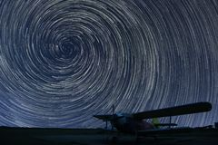Beautiful night sky, Spiral Star trails over small airport airplane. Stock Images