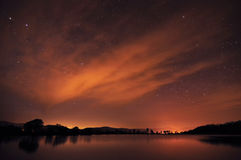 Beautiful night sky with stars, clouds and reflections in the wa Stock Photos