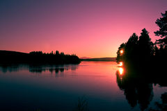 Beautiful night in the Swedish mountains. A beautiful night with a pink sky and the sun reflected in water Stock Images