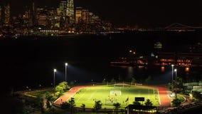Beautiful night time big city light steady time lapse panorama of New York Manhattan downtown baseball field cityscape stock footage