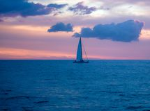 Sail boat at sunset on open waters in the Pacific Ocean royalty free stock image