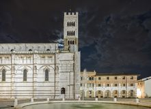 Beautiful night view of the Cathedral of San Martino with cloudy sky from which the moon appears, Lucca, Tuscany, Italy stock image