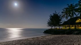 Beautiful night view of a a paradise beach with silver glow of moonlight reflecting off of water. royalty free stock photo