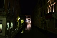 Beautiful night view to a Venice canal with reflection in water and ancient buildings. stock image