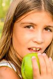 Beautiful nine year old girl eating apple. Beautiful nine year old girl is eating apple royalty free stock images