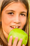 Beautiful nine year old girl  eating apple Stock Photos
