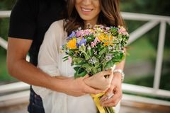 Beautiful no face portrait of couple in love with bouquet of flowers Royalty Free Stock Photography