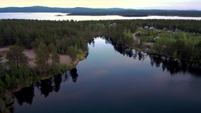 Beautiful northern landscape in the evening bird`s-eye view. Drone flight over the lake and the forest. stock video footage