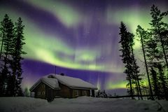 Beautiful Northern Lights Aurora Borealis in the night sky over winter Lapland landscape, Finland, Scandinavia. Beautiful purple and green Northern Lights Aurora stock photo