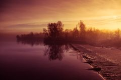 A beautiful Norwegian autumn scenery. Misty morning on a lake. Water flowing over the dam, waterfall. Beautiful, colorful autumn landscape. Vivid colors stock image