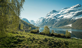 Beautiful norwegian landscape with old farm, lake and mountains Stock Image