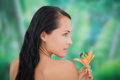 Beautiful nude brunette smelling lily Royalty Free Stock Photography