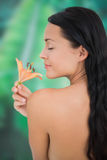 Beautiful nude brunette smelling lily Stock Photo
