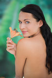 Beautiful nude brunette smelling lily Stock Photography