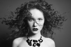 Beautiful nude woman with black jewelry. Fashion portrait. Beautiful young woman with black jewelry and curly-hair on grey background. Nude pretty lady with stock photography