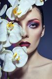Beautiful Nude woman with a branch of white Orchid in her hands,. Bright contrasting makeup on the eyes and lips. Contrasting colored purple eye shadow on the Stock Images