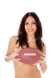 Beautiful nude woman holding american football ball. Beautiful woman nude holding an american football isolated over white background Stock Photography