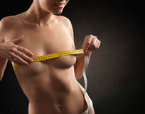 Beautiful nude woman measuring her breasts Stock Image