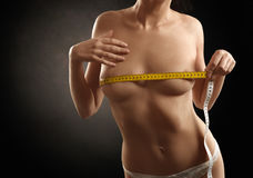 Beautiful nude woman measuring her breasts Royalty Free Stock Photo