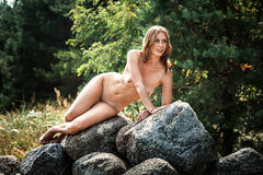 Beautiful nude woman sitting on stones Stock Images