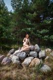 Beautiful nude woman sitting on stones Stock Photo